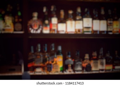 Defocused blurred picture of many bottles of liquor and whisky on the shelf in the bar at the restaurant. Party and celebration concept. Alcoholism concept. Drink don't drive campaign.