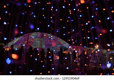 Defocused bokeh of LED lights and silhouette of people in new year night celebration