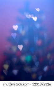 Defocused Christmas tree with heart shaped bokeh. Festive holiday background.