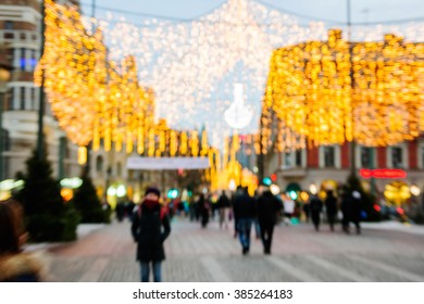 Defocused city of Malmo, Sweden with Christmas decorations and pedestrian passing near Davidshallsbron - Funny shoe bridge