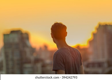 Defocused cityscape background. Gorgeous warm bokeh. Man on the sunset background.