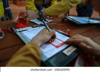 Defocused of construction miners worker hand holding pencil writing name and sign on personnel red danger tag prior placing locking into safety isolation permit control lock box
