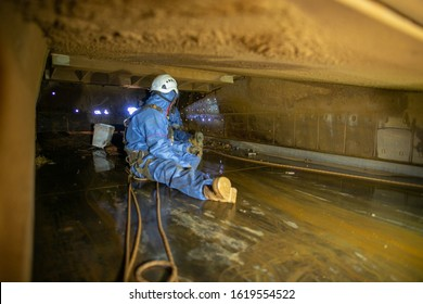 Defocused construction worker wearing safety harness disposable contaminate protective clothing connecting Karabiner which attached harness loop rescue precaution while working in confined spaces