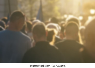 Defocused crowd attending political meeting, large group of of unrecognizable people as audience to politician's speech outdoors