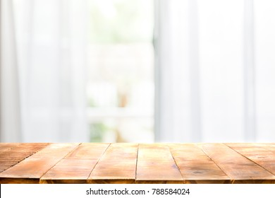 Defocused curtain window and empty of wood table top with warm sunlight. Can be used as mock up or copy space for product presentation