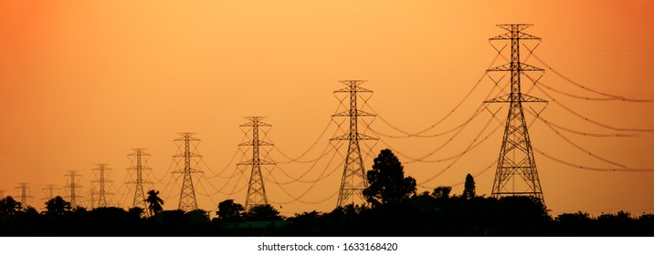 De-focused electricity transmission towers in countryside at sunset, panoramic landscape