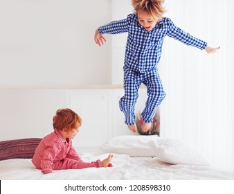defocused. excited kids, brothers playing in bedroom, jumping on bed in pajamas