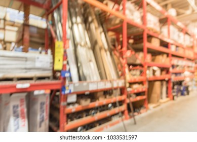 Defocused home improvement retailer with racks of roofing, flashing, coating, felt, ventilation, and metal sheeting. Blurred a large hardware store in America.