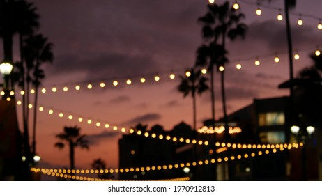 Defocused illuminated electric garland, palm trees silhouettes, Oceanside California USA. Ocean beach tropical pink sunset, pacific coast purple twilight sky. Los Angeles vibes. Bulb lights glowing.