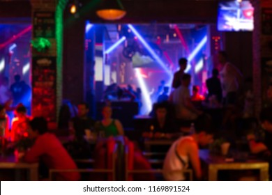 Defocused image - Blurred people with colourful laser lights inside disco club in background