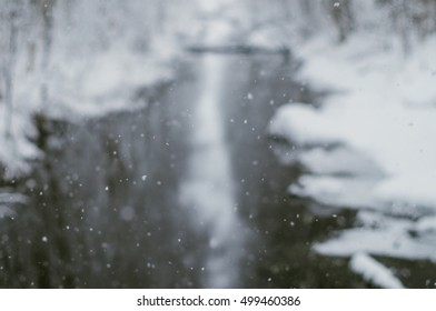 Defocused image of natural falling snow against river