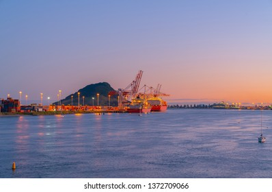 Defocused lights of Port of Tauranga ships and harbor at dawn with golden glow of sun on horizon.