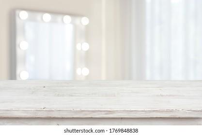 Defocused makeup mirror in dressing room with wooden table top
