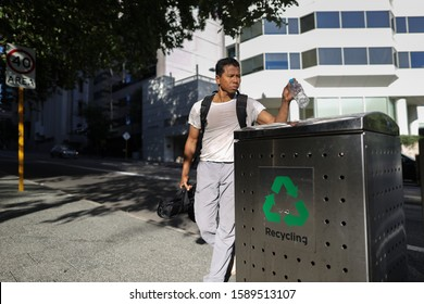 Defocused of male Asian traveller dressing a white t- shirt, gray pant, carrying a black bags standing placing empty plastic water bottle into waste recycle bin Perth city CBD, Austarlia