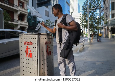 Defocused of male Asian traveller dressing a white t- shirt, gray pant, carrying a black bags standing placing empty plastic water bottle into waste bin Perth city CBD, Australia