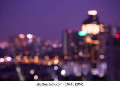 Defocused modern cityscape at night light background, blur urban skyscraper landscape twilight