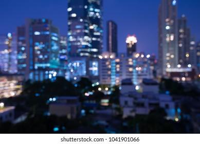 Defocused modern cityscape at night light background, blur urban skyscraper landscape