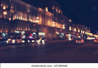 defocused night city life: cars, cyclist and street lamps