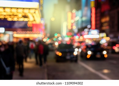 Defocused night life scene background, with lights from buildings and cars illuminating scene. Busy night in New York City.