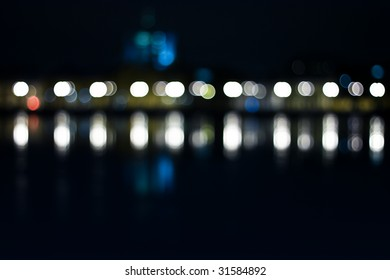 De-focused panorama of european city. Reflection on river.
