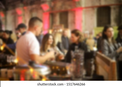 Defocused people at the event standing near the bar and barman. Blurred indoor event background.