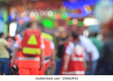 defocused photo of emergency medical services personell at funfair