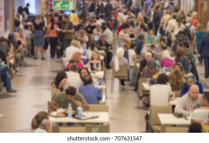 Defocused picture of crowd of people at a food court of a shopping mall