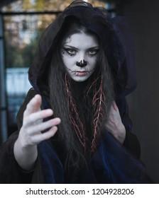 Defocused portrait halloween witch in darkness with hand