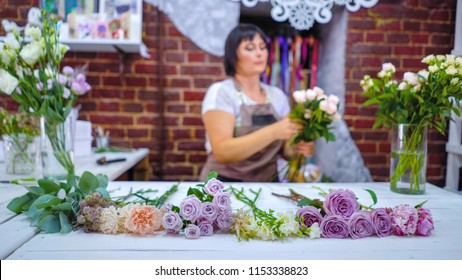 Defocused professional caucasian female florist master preparing and selecting rose branches for flower bouquet arrangement in floral design studio. Floristry, handmade and small business concept