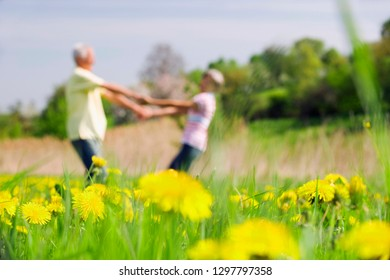 Defocused senior couple holding hands on walk in countryside