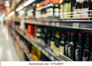 Defocused shelves with liquor wine bottles in supermarket. Liquor wine store shelf out of focus
