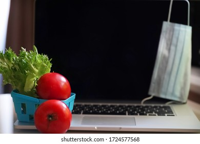 Defocused Shopping online, on the table a laptop and a blue shopping basket with tomatoes and green lettuce. A medical face mask is hanging on a laptop. Selective focus.