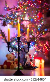 Defocused silhouette of new year advent candle holder and burning flame on illuminated fir background. Vibrant colored indoors vertical image. Low point of view.