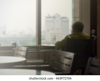 Defocused of  Silhouette old man patient lonely on a wheel-chair looking out the window. ( blur for background )