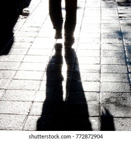 Defocused silhouette and shadow of  one man's legs walking alone on wet city street with reflection and blur after the rain in black and white