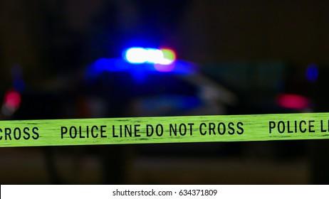 Defocused siren on police car flashing, crime scene boundary tape