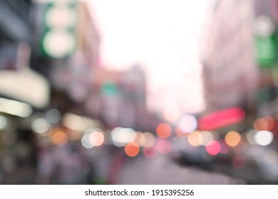 Defocused street light photo, blurry road building car and people with colourful bokeh, light are red white pink and orange.