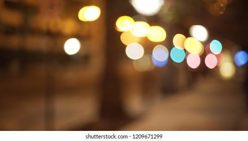 Defocused view of empty city street with flickering bokeh lights
