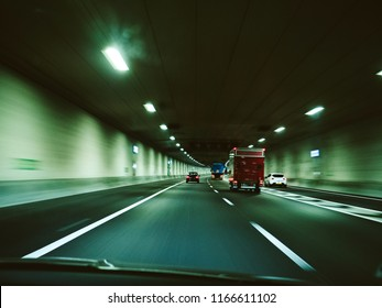 Defocused view of fast car driving in Netherlands illuminated tunnel near Amsterdam The Hague green cast mode
