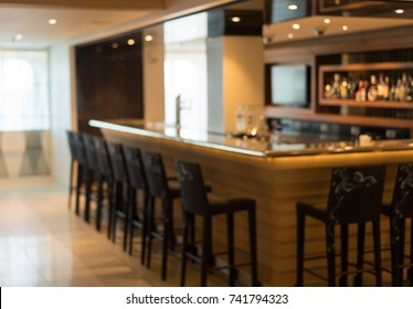 Defocused view of interior of an upmarket bar with stools surrounding the bar counter