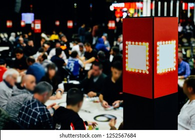Defocused view of large multi table poker tournament. Players sitting at table and dealers dealing cards.