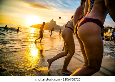Defocused view of sunset on ipanema beach in Rio de Janeiro with two ladies in bikinis and guys playing beach soccer with two brothers mountain backdrop