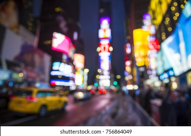 Defocused view of Times Square signage, taxi traffic, and holiday crowds in the lead-up to New Year's Eve in New York City, USA