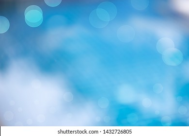 Defocused of  water surface and blue tiles floor at the bottom of  swimming pool with bokeh and white cloud reflection ,used for background.Bokeh of water in the pool.