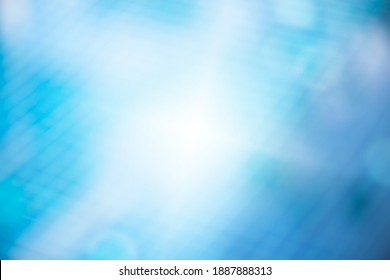Defocused of  water surface and blue tiles floor at the bottom of  swimming pool with bokeh and white cloud reflection ,used for background. Bokeh of water in the bluish pool.