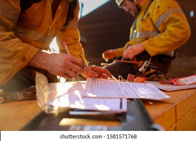 Defocused worker hand checking on JHA Job Hazard Analysis before signing hot work permit to work on isolation safety control lock box prior to work defocused senior supervisor seating background