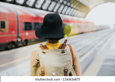 Defocussed of young backpacker hipster woman waiting for the train at platform in train station. Holiday vacation jouney concept.