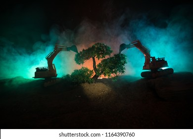 Deforestation of forest. Excavator used to dig up tree-stumps and roots after the forest was removed. Dark toned with fog table decoration. Conceptual. Selective focus