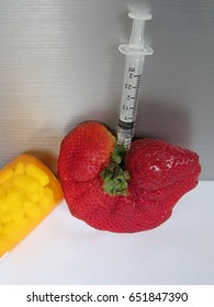 Deformed strawberry with pills and syringe concept for genetically modified food
