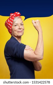 Defy age concept: mature woman with clenched fist rolling up her sleeve, background template, copy space